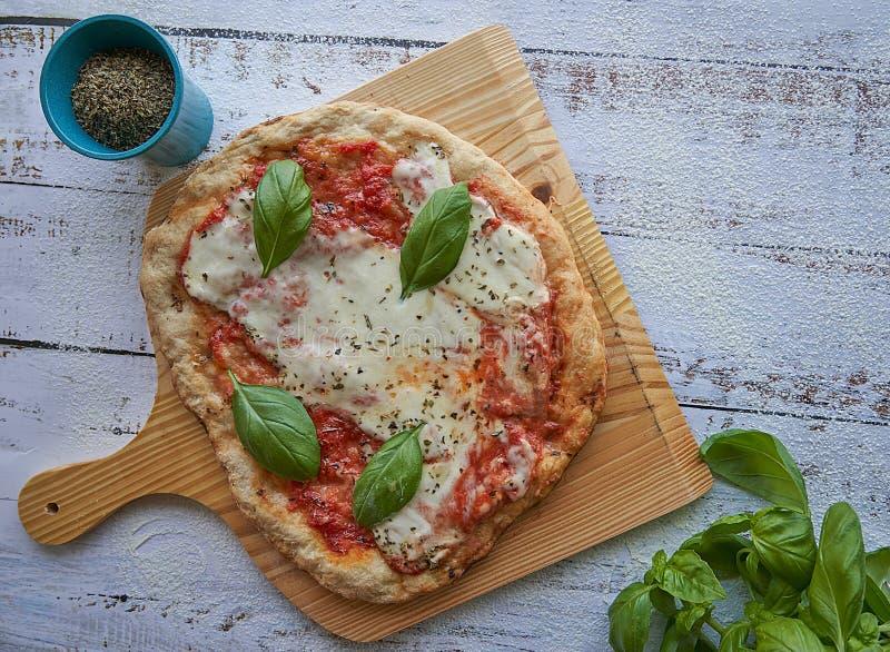 Eigengemaakte pizza met verpletterde verse tomatensaus, mozarellakaas en padano en basilicum stock foto's