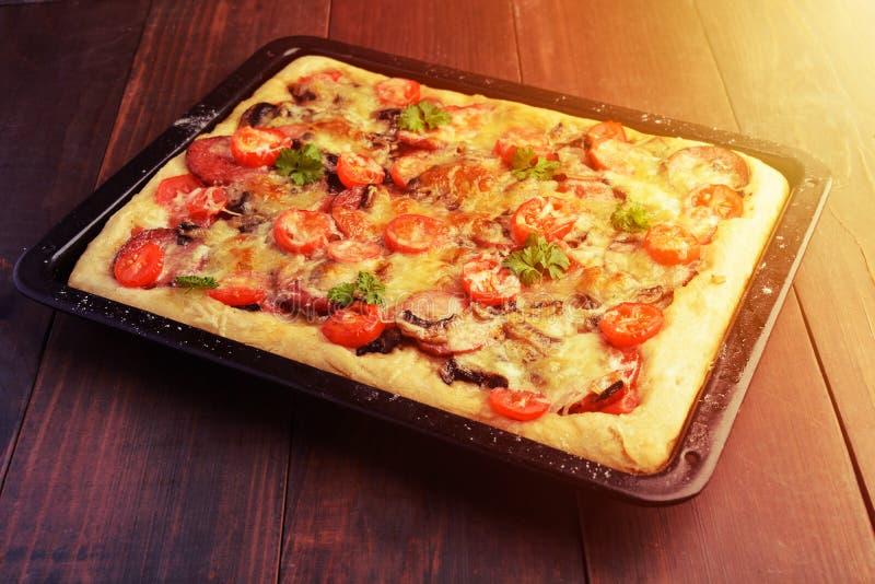 Eigengemaakte pizza op bakselpan over houten achtergrond stock foto's