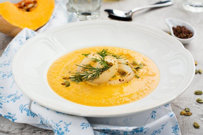 Eigengemaakte pompoen en wortelsoep met pijlinktvisringen, zaden en dille royalty-vrije stock afbeeldingen