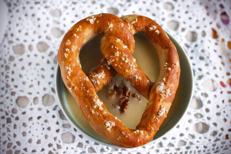 Eigengemaakte pretzel op een kom kikkererwtensoep met okkernoten royalty-vrije stock fotografie