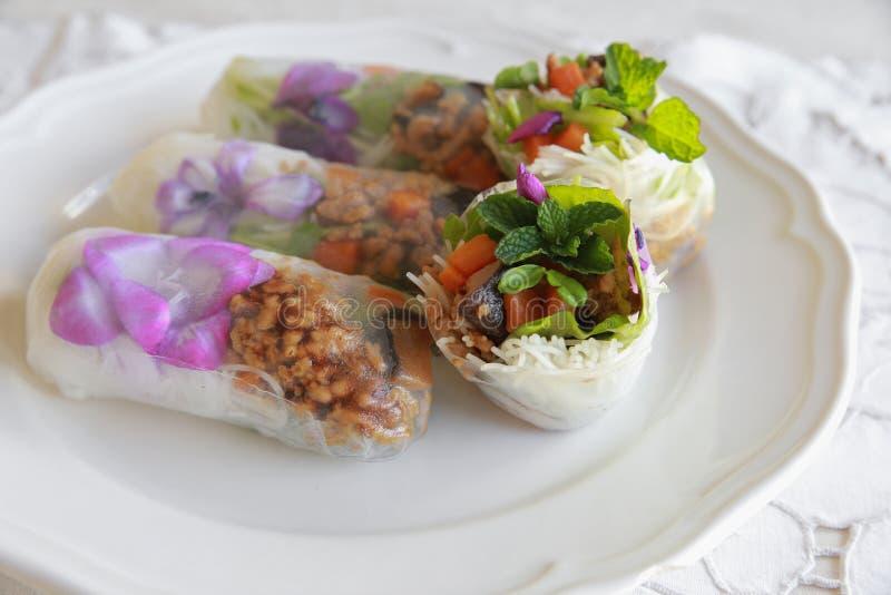 Eigengemaakte rijstpapierbroodjes met eetbare bloemen stock afbeeldingen