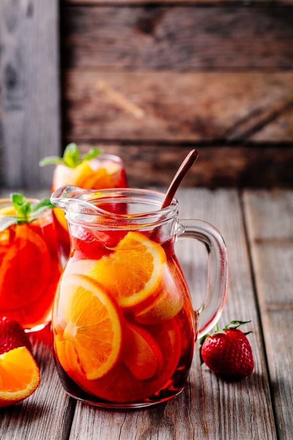 Eigengemaakte rode wijnsangria met sinaasappel, appel, aardbei en ijs in waterkruik en glas op houten achtergrond royalty-vrije stock foto