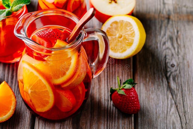 Eigengemaakte rode wijnsangria met sinaasappel, appel, aardbei en ijs in waterkruik en glas op houten achtergrond stock foto's