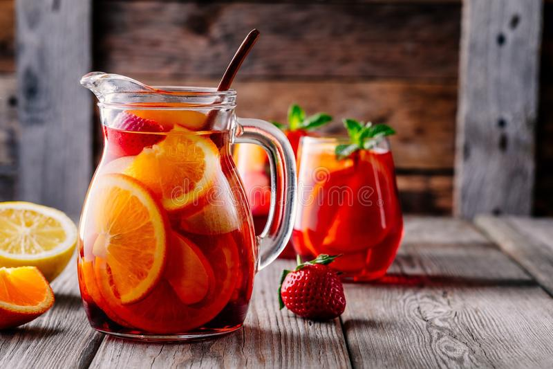 Eigengemaakte rode wijnsangria met sinaasappel, appel, aardbei en ijs in waterkruik en glas op houten achtergrond royalty-vrije stock fotografie