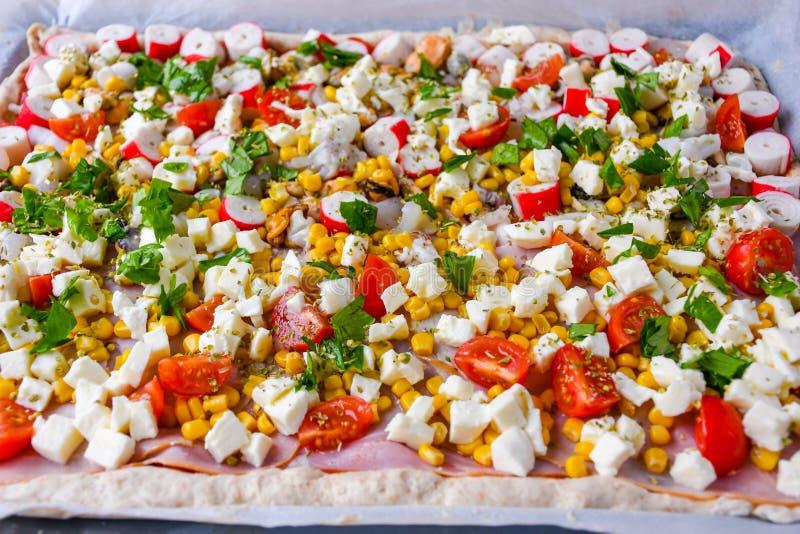 Eigengemaakte ruwe pizza met kleurrijke groenten en witte mozarellakaas enkel klaar voor de oven royalty-vrije stock foto's