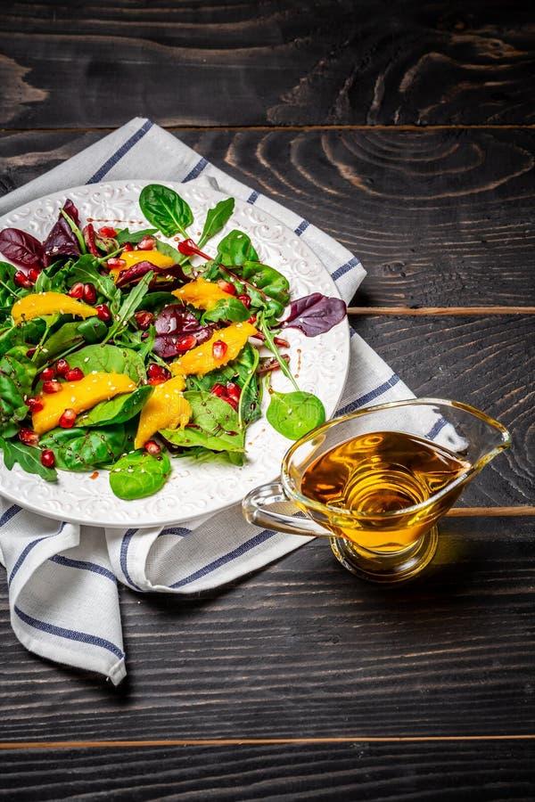 Eigengemaakte salade van verse sla, mango, granaatappel en sesam op plaat Gezond voedsel, dieet, detox, het schone eten en vegeta stock foto's