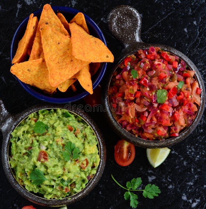 Eigengemaakte salsa en guacamole met graanspaanders stock afbeeldingen