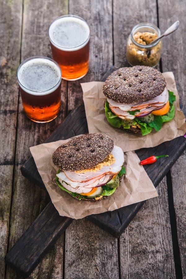 Eigengemaakte sandwich met ham en een glas bier op een oude achtergrond, hoogste mening stock foto