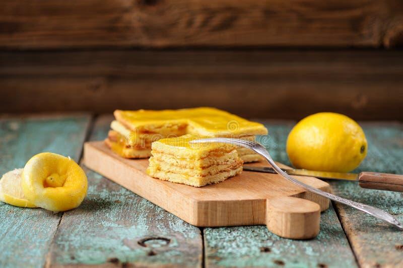 Eigengemaakte smakelijke gelaagde citroencake en gehele en gedrukte citroenen royalty-vrije stock afbeelding