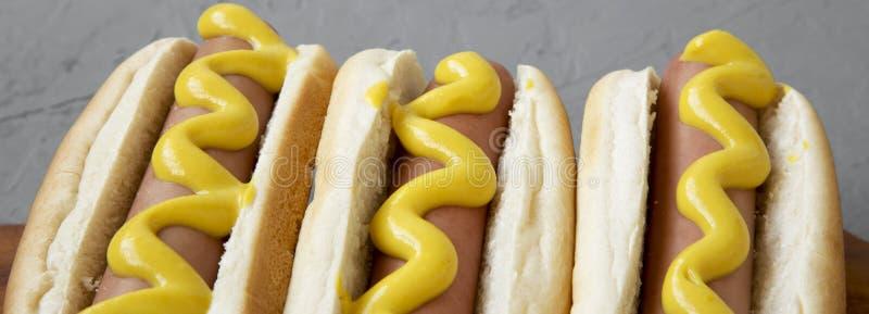 Eigengemaakte smakelijke hotdogs met gele mosterd op een rustieke houten raad op een grijze achtergrond, zijaanzicht Close-up royalty-vrije stock afbeeldingen