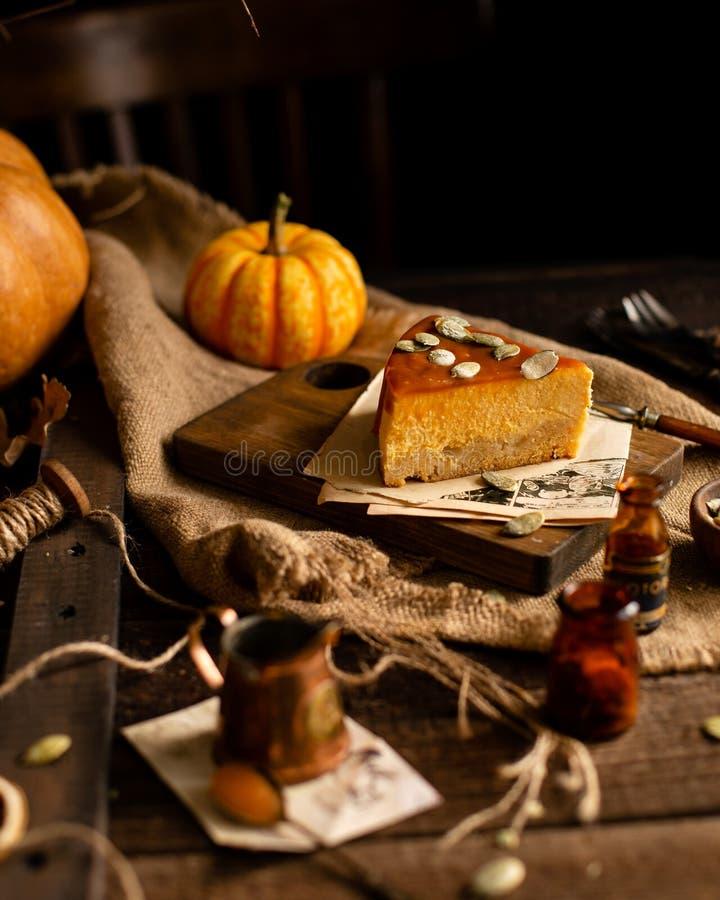 Eigengemaakte smakelijke plak van pompoen oranje kaastaart op houten raad op rustieke bruine lijst stock foto's