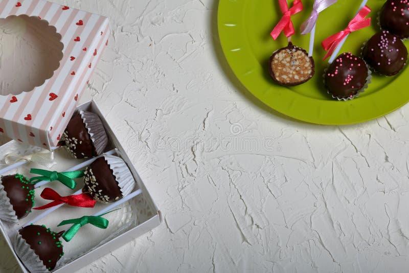 Eigengemaakte snoepjes De cake knalt verfraaid met een boog van vlecht Op de oppervlakte met decoratief pleisterwit dat wordt beh royalty-vrije stock afbeelding