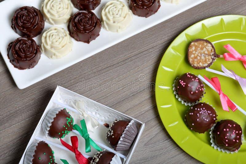 Eigengemaakte snoepjes Met chocolade bedekte snoepjes met amandel het vullen De cake knalt verfraaid met een boog van vlecht royalty-vrije stock foto's