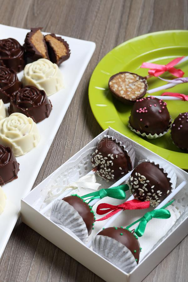 Eigengemaakte snoepjes Met chocolade bedekte snoepjes met amandel het vullen De cake knalt verfraaid met een boog van vlecht stock afbeeldingen