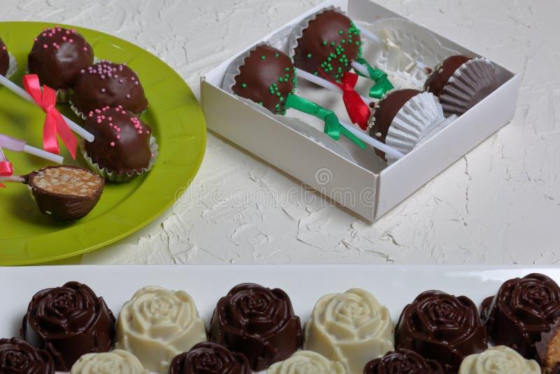 Eigengemaakte snoepjes Met chocolade bedekte snoepjes met amandel het vullen De cake knalt verfraaid met een boog van vlecht Op d royalty-vrije stock foto