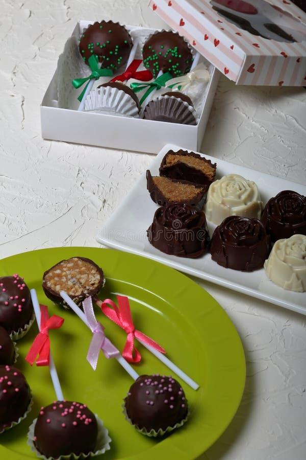 Eigengemaakte snoepjes Met chocolade bedekte snoepjes met amandel het vullen De cake knalt verfraaid met een boog van vlecht Op d stock afbeeldingen