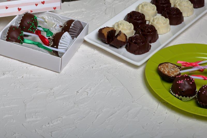 Eigengemaakte snoepjes Met chocolade bedekte snoepjes met amandel het vullen De cake knalt verfraaid met een boog van vlecht Op d stock foto's