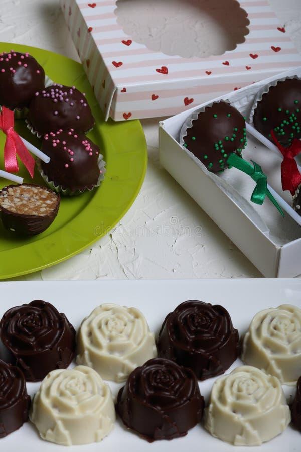 Eigengemaakte snoepjes Met chocolade bedekte snoepjes met amandel het vullen De cake knalt verfraaid met een boog van vlecht Op d stock foto