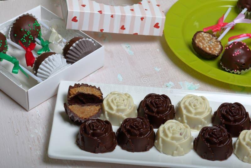 Eigengemaakte snoepjes Met chocolade bedekte snoepjes met amandel het vullen De cake knalt verfraaid met een boog van vlecht Op e royalty-vrije stock afbeeldingen