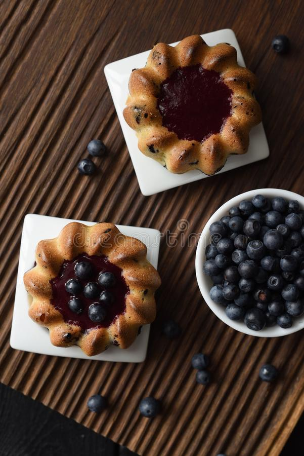Eigengemaakte snoepjes Yummy cakes met jam en de wilde bosbessen op geribbelde eiken scherpe raads hoogste mening kopiëren ruimte royalty-vrije stock foto's