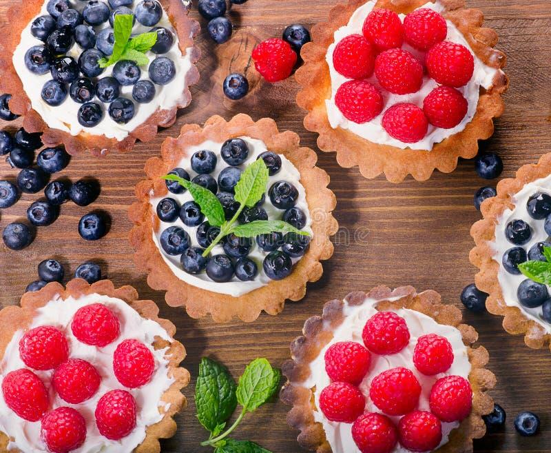 Eigengemaakte taartjes met frambozen en bosbessen op een houten lusje royalty-vrije stock fotografie