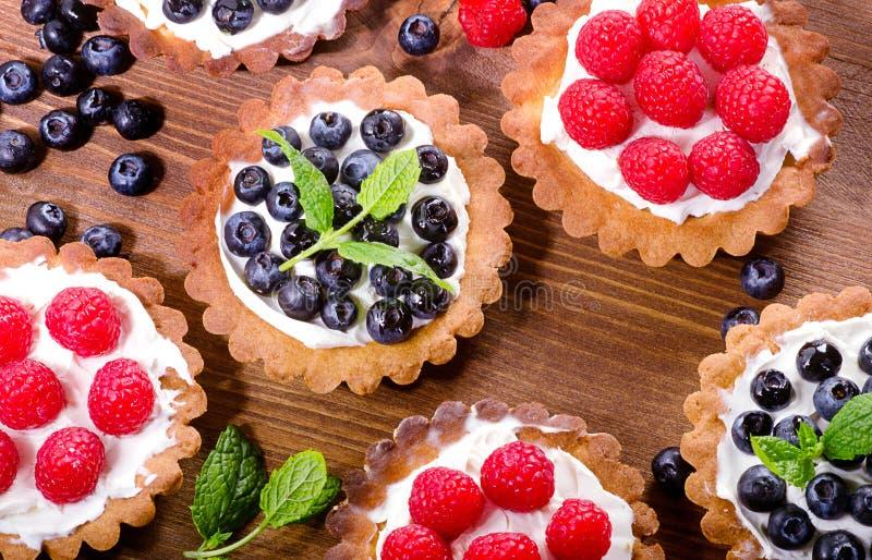 Eigengemaakte taartjes met frambozen en bosbessen op houten backg royalty-vrije stock afbeelding