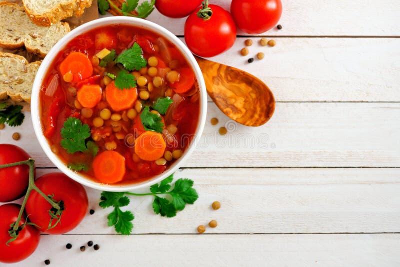 Eigengemaakte tomaat, linzesoep, hierboven, hoekgrens op wit hout stock foto's