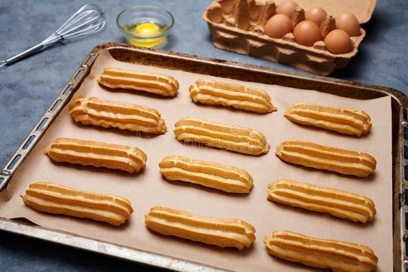 Eigengemaakte traditionele eclairs of profiterole het voorbereiden van recept op bakselblad stock foto's