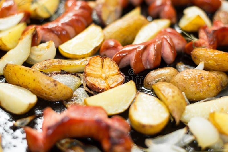 Eigengemaakte traditionele worsten en aardappels als achtergrond in een zwarte pan Vettig voedsel royalty-vrije stock afbeelding