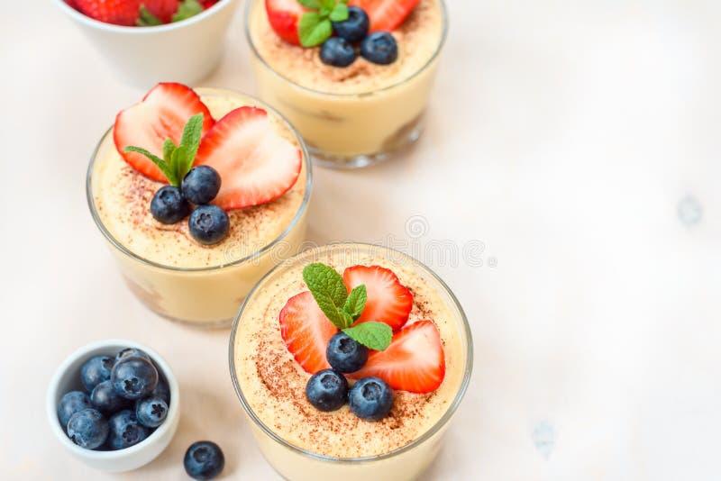 eigengemaakte, uitstekende die desserttiramisu in glazen met aardbei, bosbes, munt op witte houten lijst, hoogste mening worden v stock afbeeldingen