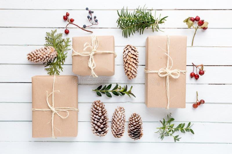 Eigengemaakte verpakte rustieke pakpapierpakketten met diverse natuurlijke dingen op witte houten oppervlakte royalty-vrije stock afbeelding