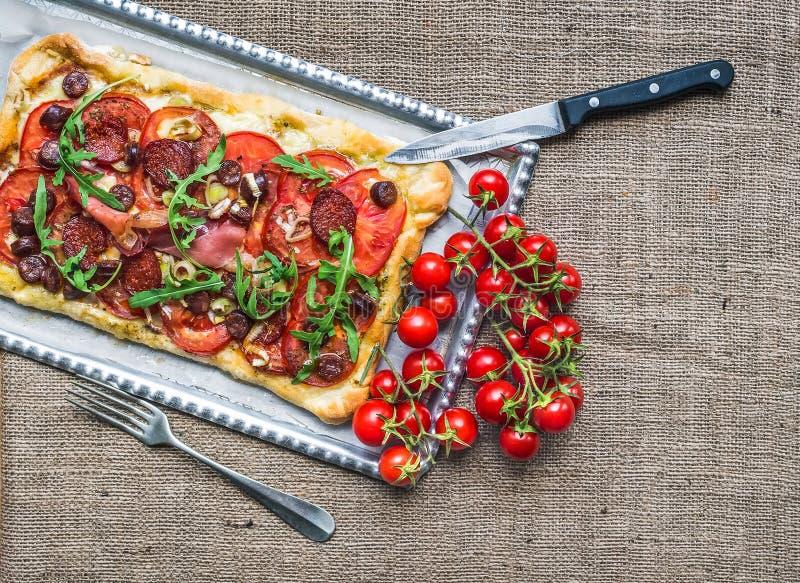 Eigengemaakte vierkante pizza met vlees, salami, kers-tomaten en fre stock afbeelding
