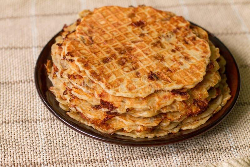 Eigengemaakte wafels met gebraden uien, champignons en kaas stock afbeelding