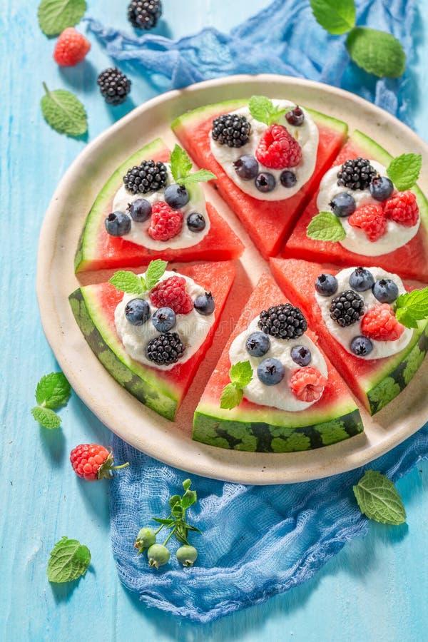 Eigengemaakte watermeloenpizza met slagroom en verse bessen stock foto's