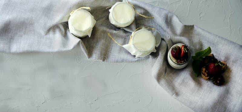 Eigengemaakte yoghurt met verse aardbeien De ingredi?nten voor een gezond ontbijt zijn de helften van aardbeien, okkernoten en yo royalty-vrije stock foto