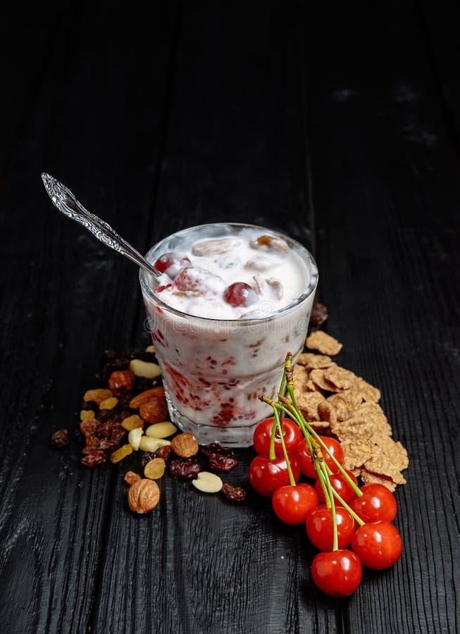 Eigengemaakte yoghurt met vlokken, noten en bessen van frambozen en kersenlepel voor het eten in glas stock afbeeldingen
