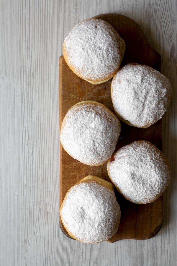 Eigengemaakte zoete donuts met gelei en gepoederde suiker op rustieke houten raad over witte houten achtergrond, luchtmening De r stock afbeeldingen
