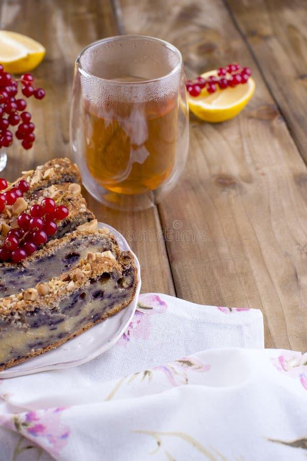 Eigengemaakte zoete pastei voor ontbijt met citroen en bessen van zwarte bes en rode aalbes Een glas thee Bruine houten achtergro stock afbeeldingen