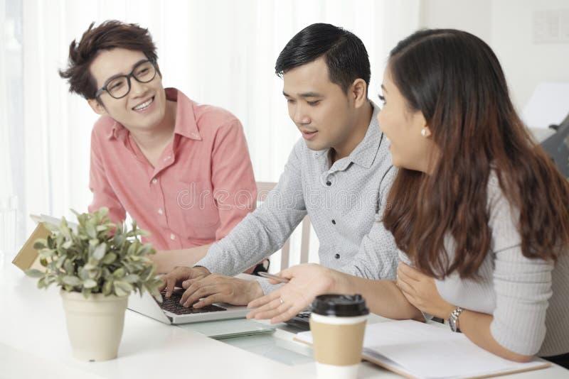 Eigentijdse Aziatische medewerkers met laptop bij bureau stock afbeeldingen