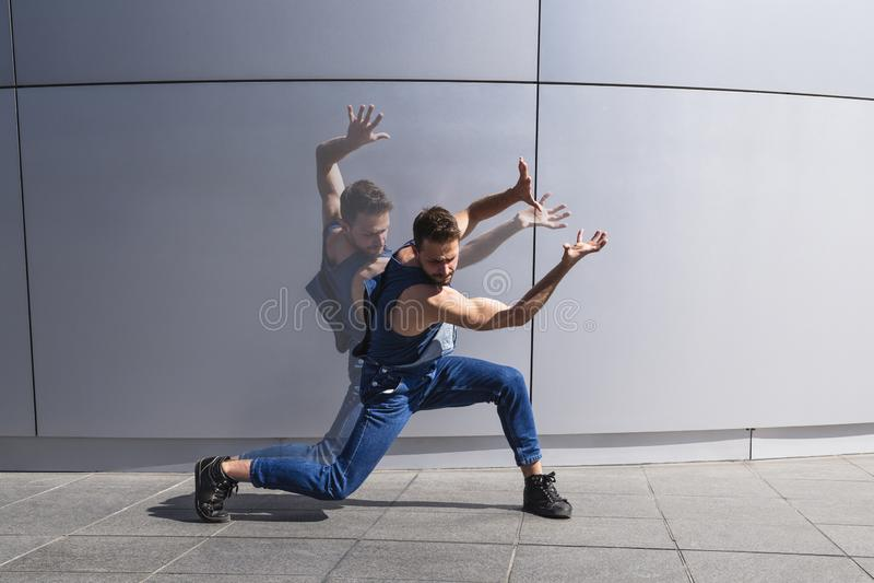 Eigentijdse danser die met dubbele schaduw op minimalistic achtergrond dansen stock foto's