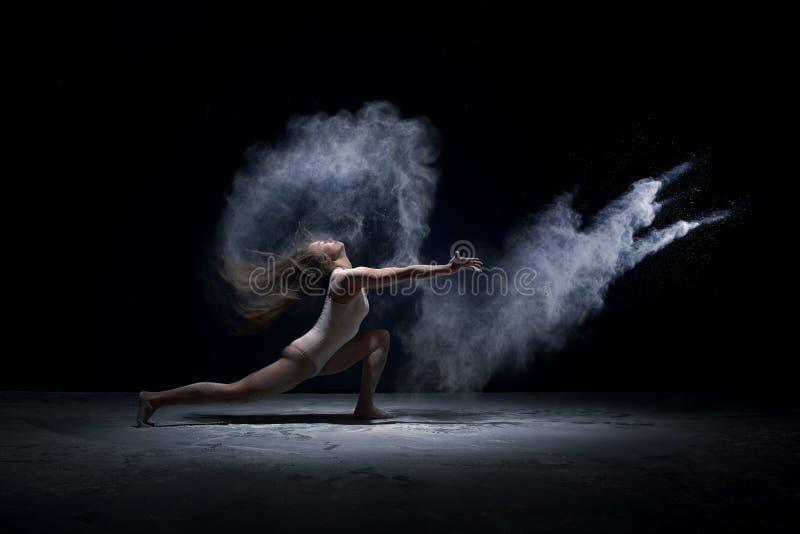 Eigentijdse danser die in wolk van poeder presteren stock foto