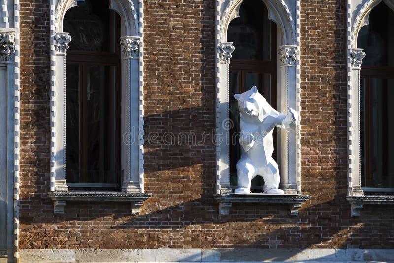 Eigentijdse kunst: het beeldhouwwerk van een wit draagt bevindend in een venster stock fotografie