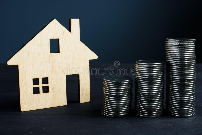 Eigentums-Investition und Wert des Hauses Münzen und Modell des Hauses stockfotos