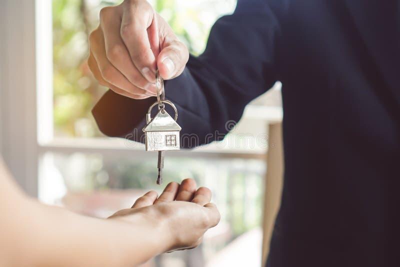 Eigentumsgrundstücksmakler/-hauseigentümer, der Käufer/dem Pächter Schlüsselhaus gibt lizenzfreie stockfotografie