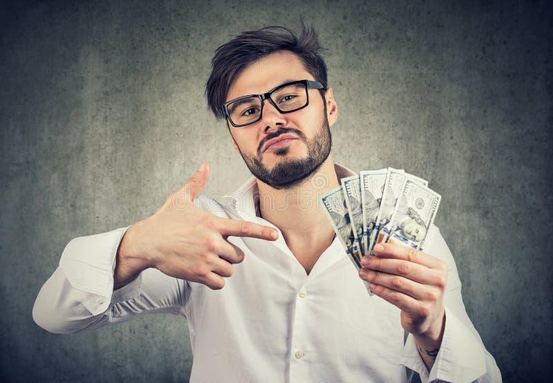 Eigenwijze mens met stapel van geld royalty-vrije stock afbeeldingen
