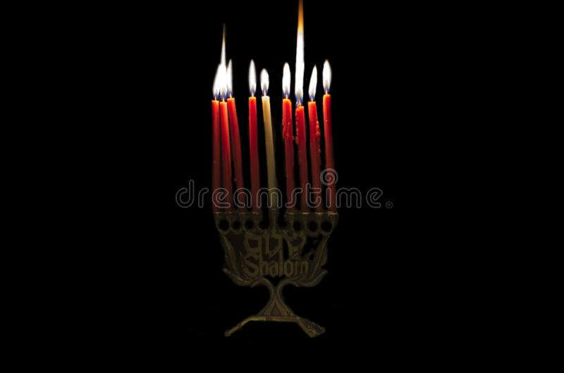 Eight burning candles on traditional jewish candelabra menorah royalty free stock images
