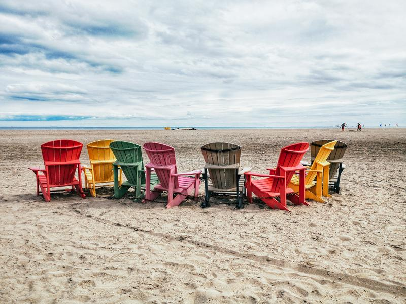 Eight many colorful red, brown and yellow wooden muskoka Adirondack chairs in row on beach outside. Concept of relaxation and calm talk conversation among stock photography