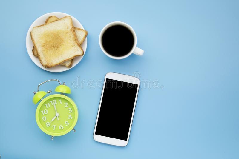 Eight o`clock green clock and toast black coffee with mobile pho royalty free stock image