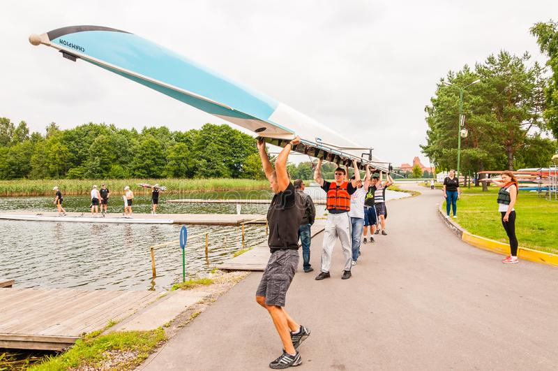 Eight people carrying an eight that is a rowing boat used in the sport of competitive rowing. This summer touristic attraction is stock photos