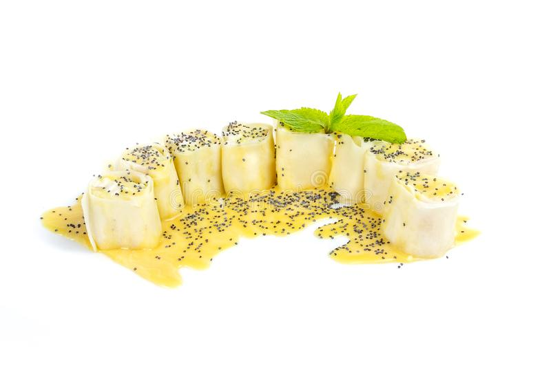 Eight pieces of sushi like cakes with vanilla topping and poppy seeds isolated on white background.  royalty free stock photography